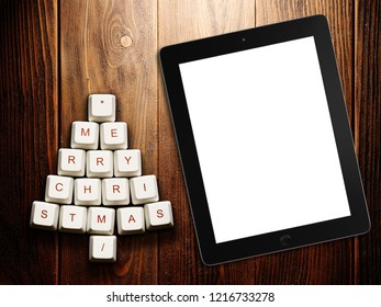 Christmas tree made of computer keys and tablet computer on wooden background . 3d rendering