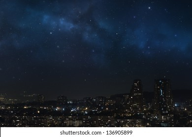 City landscape at nigh with sky filled with stars, nebula and galaxy
