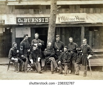 "Civil War. Ambrose Everett Burnside with eight officers of the lst Rhode Island Volunteers, with sign reading ""Col. Burnside welcome home."" Camp Sprague, District of Columbia, 1861"