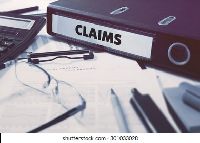Claims - Ring Binder on Office Desktop with Office Supplies. Business Concept on Blurred Background. Toned Illustration.