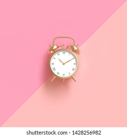 classic gold-colored alarm clock on a two-tone pink background. Flat lay style. 3d image render.