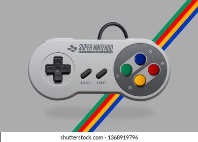 Classic retro gaming console gamepad from Super Nintendo Entertainment System on a gray background, with color stipes that matches the console color theme.
