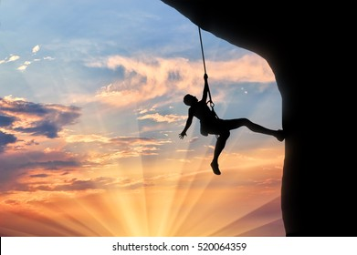 Climber on the rope climbs cliff sunset. Concept of mountaineering