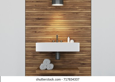 Close up of an angular sink in a wooden and white bathroom interior. There is a wooden shelf with rolled up towels and a round lamp. 3d rendering mock up