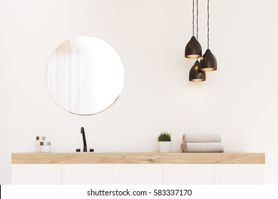 Close up of a bathroom sink, a round mirror and a towel. There is a wooden decoration element. Concept of modern luxury interior. 3d rendering. Mock up.