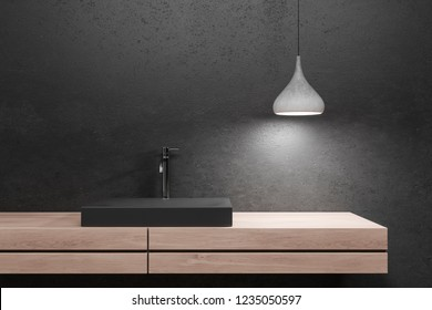 Close up of black bathroom sink standing on wooden countertop in room with black walls and stylish ceiling lamp. 3d rendering