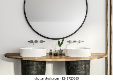 Close up of black round double sink standing on wooden shelf in bathroom interior with white walls and big round mirror. 3d rendering