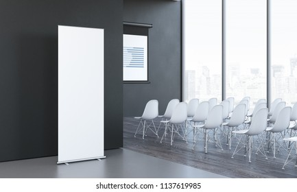 Close up of blank white roll up next to meeting room in modern office with black walls, large windows and white chairs, 3d rendering