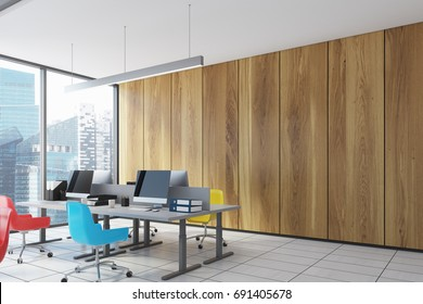 Close up of a computer table in a wooden wall open space office with panoramic windows, columns and colored chairs. 3d rendering mock up