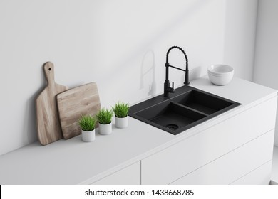 Close up of gray kitchen sink standing on white countertops with potted plants, cutting boards and dishes in modern room with white walls. 3d rendering
