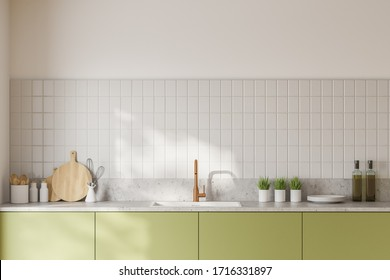 Close up of green countertops with built in sink standing in modern kitchen with white tiled walls. 3d rendering