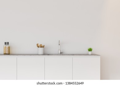 Close up of kitchen counter with built in sink and jar with wooden spoons standing in room with white walls. 3d rendering