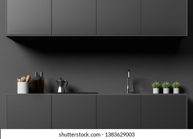 Close up of minimalistic kitchen with dark gray walls, dark gray countertops with built in sink and stove and cooking appliances and dark gray cabinets above them. 3d rendering