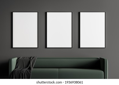 Close up modern living or waiting room interior with furnished by green sofa and three white empty posters on black wall. Minimalist design concept. 3D rendering