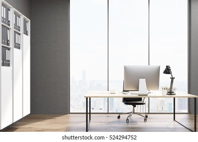 Close up of a table with a desktop on it standing in an office with white bookcase near a wall. 3d rendering. Mock up