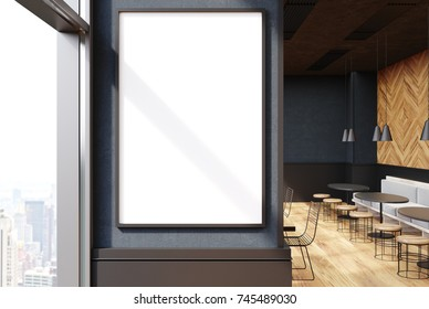 Close up of a vertical framed poster on a cafe wall. Large windows, gray and wooden walls and round tables with sofas and stools. 3d rendering mock up