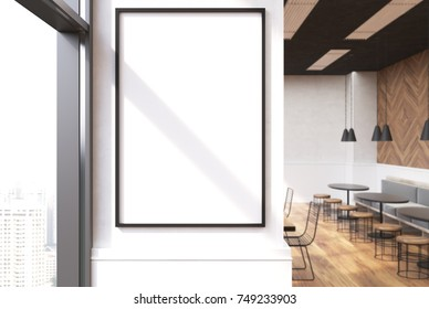 Close up of a vertical framed poster on a cafe wall. Large windows, white and wooden walls and round tables with sofas and stools. 3d rendering mock up