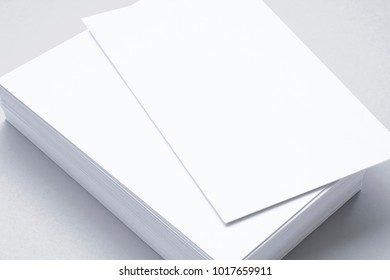 Close view of blank business cards isolated on grey. 3d illustration of vertical stacks to showcase your presentation.