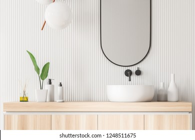 Close up of white bathroom sink standing on wooden countertop in room with white wall and narrow mirror. 3d rendering