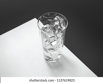 Close up of white blank sheet with transparent glass of water and ice on black background. 3d rendering