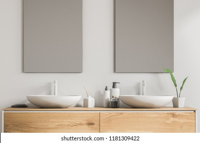 Close up of white double sink standing on a wooden vanity unit in a white wall bathroom with two vertical mirrors. Relaxation and self care concept. 3d rendering
