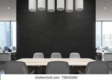 Close up of a wooden table in a meeting room of an office with a black wall, an open office area in the background and round modern ceiling lamps. 3d rendering mock up