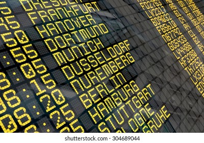 Close-up of an airport departure board to german cities destinations, with environment reflection.Part of a series.