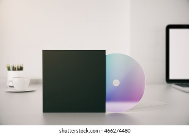 Closeup of empty black CD cover on desktop with laptop, coffee cup and pencils. Mock up, 3D Rendering