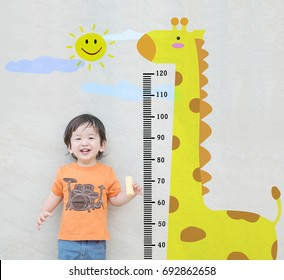 Closeup happy asian kid stand for measure height with cute cartoon at the marble stone wall textured background