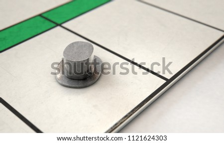 A closeup of a metal die cast hat icon on a game board  - 3D render