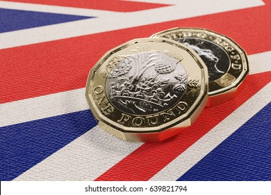 Close-up of two 2017 British pound coins resting on a British flag (3D rendering).