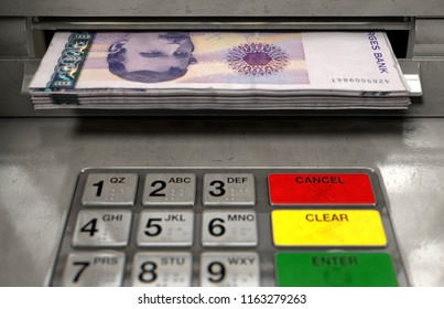 A closeup view of an atm facade with an illuminated sceen and keypad and a wad of norwegian kroner banknotes being withdrawn from the cash slot - 3D render