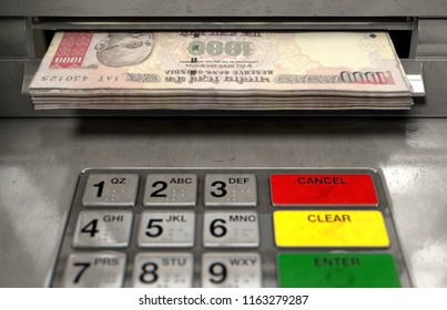 A closeup view of an atm facade with an illuminated sceen and keypad and a wad of indian rupee banknotes being withdrawn from the cash slot - 3D render
