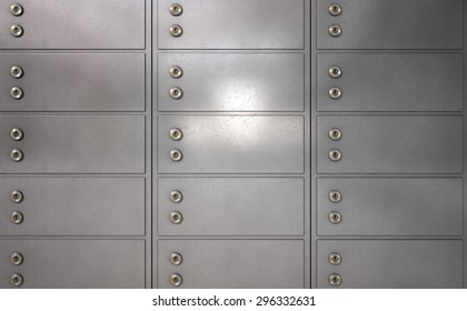 A closeup of a wall of closed metal safety deposit boxes