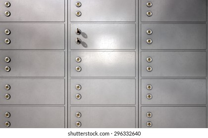A closeup of a wall of closed metal safety deposit boxes and one with two keys inserted into it