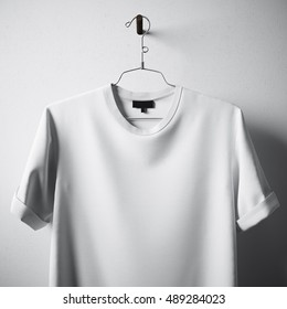 Closeup White Blank Cotton Tshirt Hanging Center Gray Concrete Empty Wall Background.Mockup Highly Detailed Texture Materials.Clear Label Space for Business Message. Square. 3D rendering