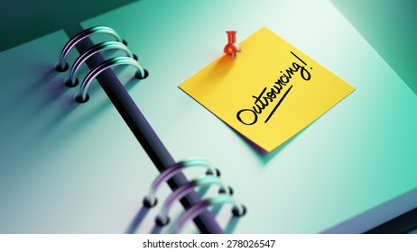 Closeup Yellow Sticky Note paste it in a notebook setting an appointment. The words Outsourcing written on a white notebook to remind you an important appointment.