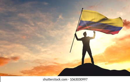 Colombia flag being waved by a man celebrating success at the top of a mountain. 3D Rendering