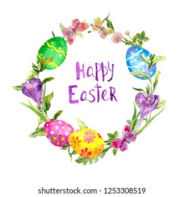 """Colored eggs in grass, crocus flowers, butterflies. Easter wreath, card. Floral circle border with text """"Happy Easter"""". Watercolor"""