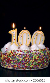 A colorful birthday cake with candles shaped like the number 100. Black background.