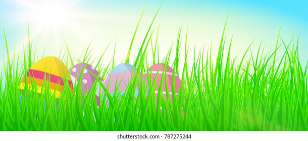 colorful easter eggs in fresh green grass against blue sky