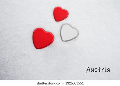 Colors of the austrian flag (Imperial Red (top/bottom) and White) painted on three hearts. Snow background with the country, Austria, written on bottom right. Concept for warm welcome in tourism.