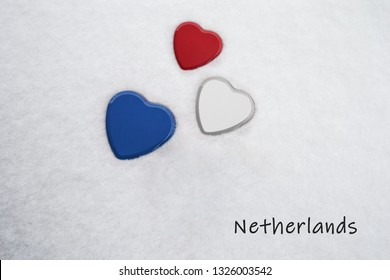Colors of the dutch flag (Upsdell Red, White, Dark Cornflower Blue) painted on three hearts. Snow background with the country, Netherlands, written on bottom right. Concept for warm welcome in tourism