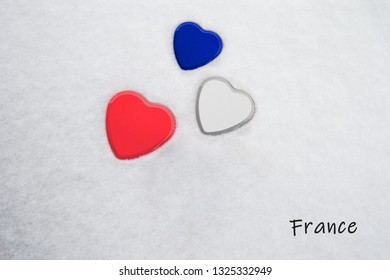 Colors of the french flag (Imperial Blue, White, Imperial Red) painted on three hearts. Snow background with the country, France, written on bottom right. Concept for warm welcome in tourism.