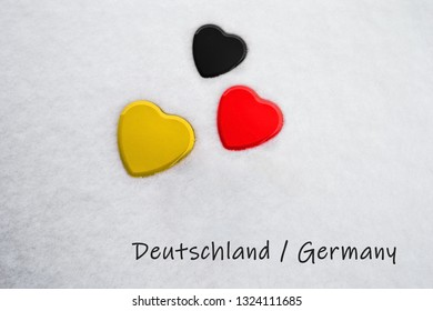Colors of the german flag (Black, Electric Red, Tangerine Yellow) painted on three hearts. Snow background with the country, Germany, written on bottom right. Concept for warm welcome in tourism.