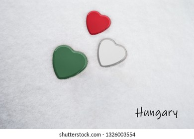 Colors of the hungarian flag (French Raspberry, White, Amazon/green) painted on three hearts. Snow background with the country, Hungary, written on bottom right. Concept for warm welcome in tourism.