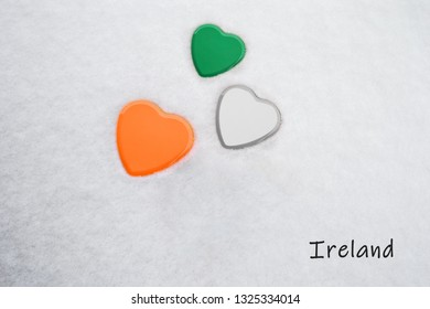 Colors of the irish flag (Shamrock Green, White, Mango Tango) painted on three hearts. Snow background with the country, Ireland, written on bottom right. Concept for warm welcome in tourism.