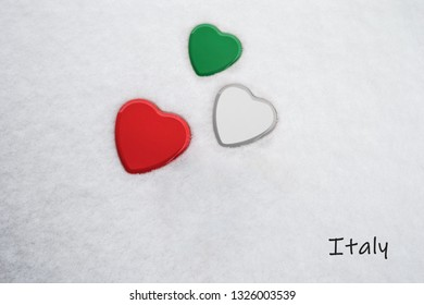 Colors of the italian flag (Spanish Green, White, Madder Lake/red) painted on three hearts. Snow background with the country, Italy, written on bottom right. Concept for warm welcome in tourism.