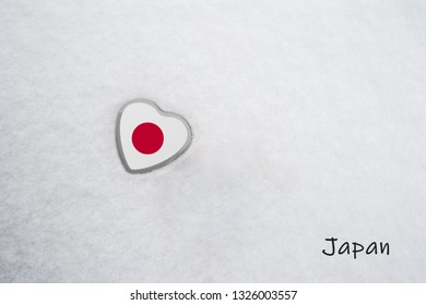 Colors of the japanese flag (Crimson Glory/red on white) painted on a heart. Snow background with the country, Japan, written on bottom right. Concept for warm welcome in tourism.