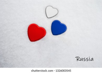 Colors of the russian flag (White, Philippine Blue, Maximum Red) painted on three hearts. Snow background with the country, Russia, written on bottom right. Concept for warm welcome in tourism.